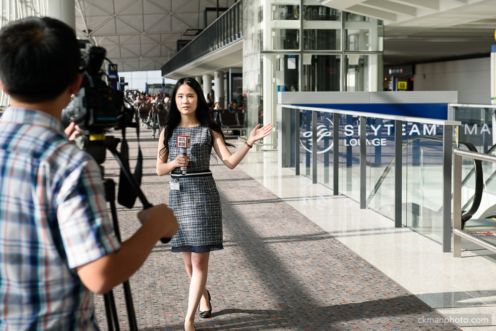 TV news reporter covering grand opening of Skyteam lounge in Hong Kong